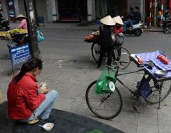Một phụ nữ bán trái cây rong ở Hà Nội đang đếm tiền hôm 27/1/2014. AFP photo