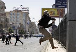 Người biểu tình chống chính phủ ở Yemen ném đá vào một trạm cảnh sát hôm 17/2/2011. AFP photo