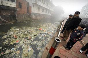 Dân địa phương đang quan sát con sông bị ô nhiễm nặng ở thành phố Zhugao tỉnh Sichuan, Trung Quốc. AFP