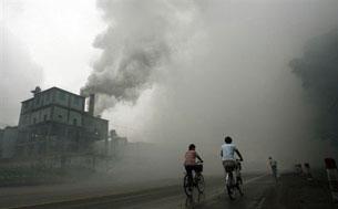 Nhà máy tại thành phố Yutian cách Bắc Kinh 100 cây số trong giờ làm việc thải khói mù mịt đường phố. AFP