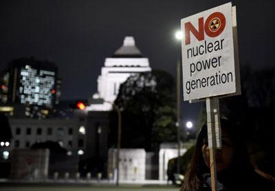 Một người dân Nhật với tấm bảng phản đối xây dựng nhà máy điện hạt nhân hôm 11/3/2016. AFP photo