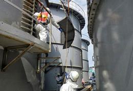 Các chuyên viên chuẩn bị tháo gỡ một bể nước rò rỉ và bị ô nhiễm chất phóng xạ tại nhà máy hạt nhân Fukushima Daiichi. Hình ảnh được chụp bởi TEPCO ngày 13 tháng 9 năm 2013