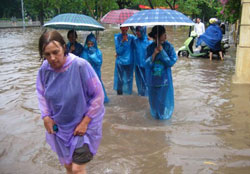 Một khách du lịch nước ngoài lội nước ngập sau trận mưa lớn tại Hà Nội hôm 13/7/2010. AFP photo
