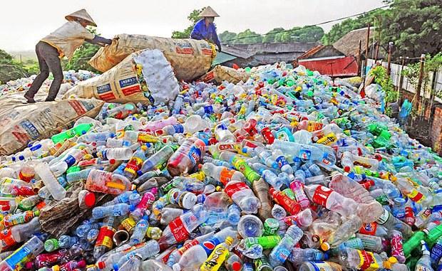 Bức ảnh này chụp vào ngày 4 tháng 10 năm 2015 cho thấy công nhân đứng trên một đống lớn các chai nhựa của một nhà kinh doanh các mặt hàng tái chế tại huyện Thạch Thất ở vùng ngoại ô của Hà Nội.