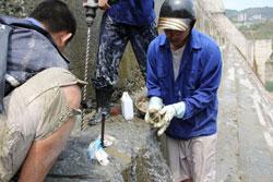 Những công nhân đang xử lý rò rỉ nước ở thủy điện Sông Tranh 2 hôm 21-03-2012. Photo courtesy of bee.vn