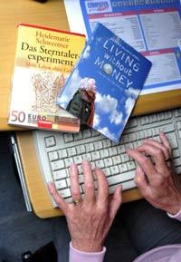"""Bà Schwermer ngồi trước máy tính với cuốn sách """"The Star-Money Experiment"""" và DVD """"Living without money"""" nói về cuộc đời bà hôm 26/7/2011. AFP"""