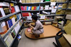 Một nhân viên của NXB Tri thức đọc sách tại văn phòng của họ tại Hà Nội hôm 31/8/2010. AFP photo