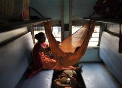 Một phụ nữ cùng các con đang di chuyển trên một chuyến xe lửa ở Ấn Độ. AFP photo