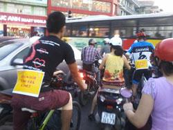 Các bạn trẻ đạp xe và đeo những khẩu hiệu sau lưng và trước ngực phản đối tăng giá xăng. Citizen photo.