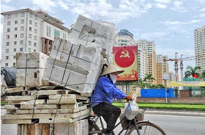 Một công nhân tranh thủ thu gom những vật dụng phế thải. AFP