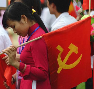 Một bạn sinh viên cầm cờ đảng trong ngày diễu binh của quân đội ở Hà Nội tháng 10/2010. AFP photo