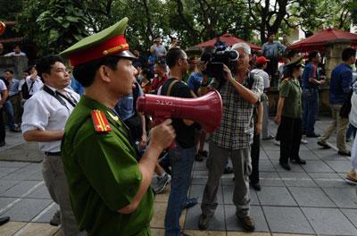 Công an dùng loa yêu cầu mọi người không tụ tập trên một đường phố gần đại sứ quán Trung Quốc tại Hà Nội ngày 18 tháng 5 năm 2014. AFP photo