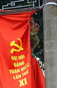 Một công nhân đang treo biểu ngữ chào mừng Đại hội Đảng Cộng sản XI ở Hà Nội ngày 04 tháng 1 năm 2011.