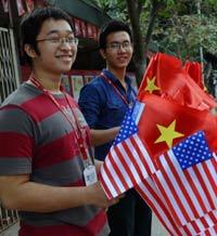 Hai sinh viên cầm cờ Hoa Kỳ và Việt Nam chào đón bà Hillary Clinton tới Hà Nội vào ngày 14 tháng 11 2010. AFP photo
