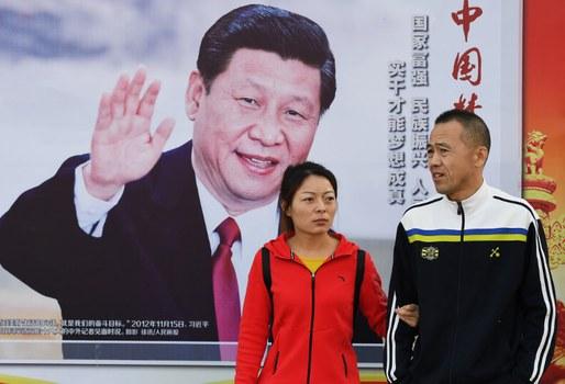 Hình minh họa. Người dân đi qua một tấm biển có hình Chủ tịch Tập Cận Bình ở Bắc Kinh trong dịp đại hội đảng 19 hôm 23/10/2017