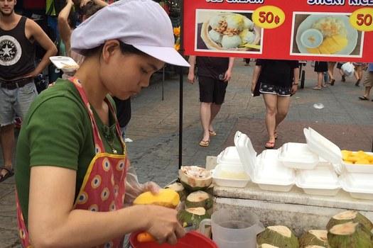 Chị Thương, quê Nghệ An, tuy mới 22 tuổi nhưng chị đã có thâm niên 4 năm bán hàng rong ở khu phố Khao San này, món hàng mà chị bán là xôi xoài và kèm dừa.