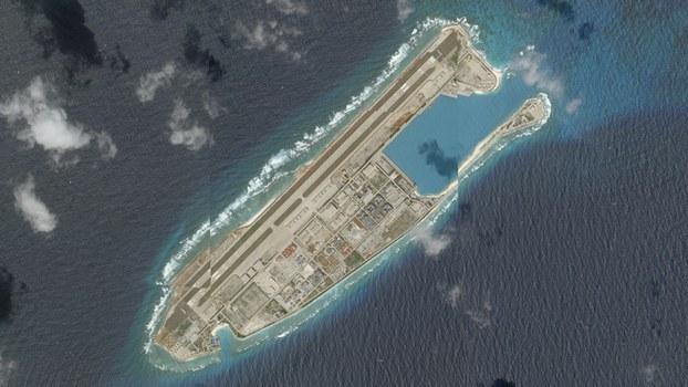 Hình chụp từ vệ tinh cho thấy tàu Nam Hải Cứu 115 đang neo tại đảo nhân tạo mà Trung Quốc xây dựng với đường băng và các bến cảng tại Đá Chữ Thập