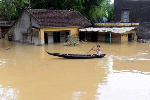 Một cậu bé chèo thuyền qua ngôi nhà bị ngập tại tỉnh Bình Định hôm 18/12/2016.