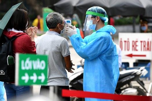 Hình minh hoạ. Một nhân viên y tế kiểm tra thân nhiệt khách đến bệnh viện Bạch Mai hôm 24/3/2020
