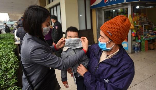 Một nhân viên tại Hà Nội hướng dẫn đeo khẩu trang cho người dân (Ảnh minh họa)