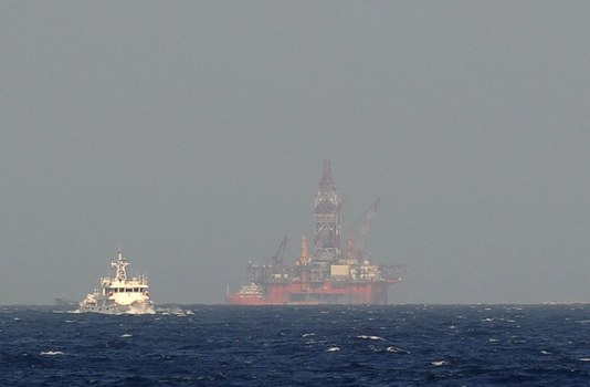 Hình chụp hôm 14/5/2014 từ tàu cảnh sát biển Việt nam cho thấy tàu hải giám của Trung Quốc (trái) đang đi gần giàn khoan dầu của Trung Quốc trong vùng nước tranh chấp ở Biển Đông.
