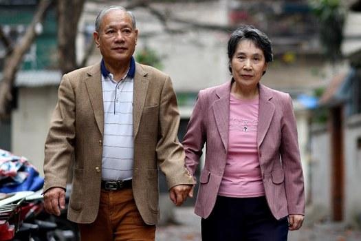 Ông Phạm Ngọc Cảnh (trái) nắm tay vợ là bà Ri Yong Hui đi bên ngoài ngõ gần nhà ở Hà Nội hôm 13/2/2019