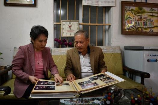 Ông Phạm Ngọc Cảnh và vợ là Ri Yong Hui đang xem ảnh cũ của hai người
