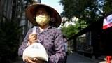 Ảnh minh họa: Một người dân nhận gạo miễn phí ở nhà thờ St. Joseph ở Hà Nội hôm 27/4/2020.