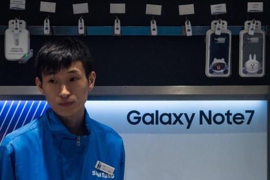 Một nhân viên bán hàng đứng bên cạnh một màn hình cho Samsung Galaxy Note 7 tại một cửa hàng Samsung tại Hồng Kông vào ngày 11 Tháng 10 năm 2016.