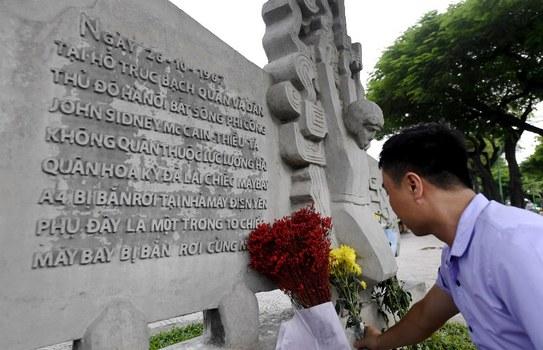 Một người Việt đặt hoa tưởng nhớ TNS John McCain ở Hồ Trúc Bạch nơi máy bay của TNS John McCain bị bắn rơi ở Hà Nội năm 1967