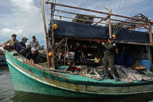 Hình minh họa. Các ngư dân Việt Nam (trái) đang ngồi trên tàu sau khi họ bị Cảnh sát Biển Thái Lan (phải) bắt giữ ở tỉnh Narathiwat hôm 14/2/2016