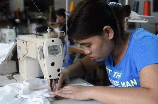 Một công nhân đang làm việc tại một xưởng may quần áo, ngoại thành Hà Nội. 2013.