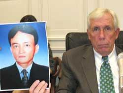 Dân biểu Frank Wolf và ảnh của nạn nhân anh Nguyễn Thành Năm, tại buổi điều trần của Ủy ban Nhân quyền Tom Lantos ở Quốc hội Hoa Kỳ, ngày 18 tháng 8. RFA PHOTO.